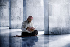 Religious muslim man reading holy koran Stock Photography