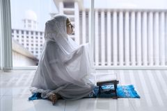 Religious Muslim woman praying to the Allah. Portrait of a religious Muslim woman praying to the Allah after reading the Quran in the mosque Stock Images