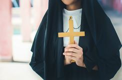 Religious nun in religion concept. Hands praying to the GOD while holding a crucifix symbol . Nun holding a cross in his hands. stock photography