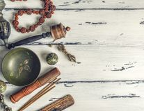 Religious objects for meditation and alternative medicine. Copper singing bowl, prayer beads, prayer drum, stone balls and other Tibetan religious objects for stock image