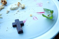 Religious Obsession with Food. Close up of a chocolate cross crucifix with mint leaf and left over cake on a white plate royalty free stock images
