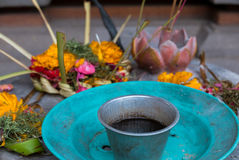 Religious offerings in Bali, colored flowers with turquoise dish. Couple Balinese colored flowers dropped on stones with turquoise dishes, religious offerings in Royalty Free Stock Image