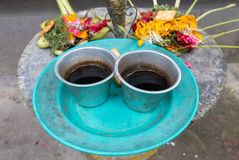 Religious offerings in Bali, colored flowers with turquoise dish Royalty Free Stock Photography