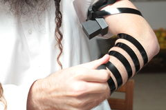 A religious orthodox Jew with arm-tefillin on his left hand prays A jewish man is preparing the tefillin. Pair of tefilin and Tallit A symbol of the Jewish Stock Photo