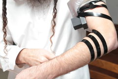 A religious orthodox Jew with arm-tefillin on his left hand prays A jewish man is preparing the tefillin. Pair of tefilin and Tallit A symbol of the Jewish Stock Photos
