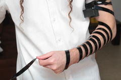 A religious orthodox Jew with arm-tefillin on his left hand prays A jewish man is preparing the tefillin. Pair of tefilin and Tallit A symbol of the Jewish Royalty Free Stock Images