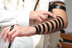 A religious orthodox Jew with arm-tefillin on his left hand prays A jewish man is preparing the tefillin. Pair of tefilin and Tallit A symbol of the Jewish Royalty Free Stock Photo