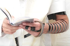 A religious orthodox Jew with arm-tefillin on his left hand prays A jewish man is preparing the tefillin. Pair of tefilin and Tallit A symbol of the Jewish Stock Images