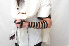 A religious orthodox Jew with arm-tefillin on his left hand prays A jewish man is preparing the tefillin. Pair of tefilin and Tallit A symbol of the Jewish Stock Image