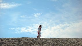 Religious outcast walking in desert, lonely tired man fasting seeking God