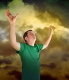 Religious Peace Man Reaching for the Sky Clouds. A man is looking up reaching his hands out into the sky representing religion, peace or God. The clouds are Stock Photo
