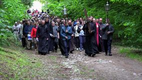 Religious people procession carrying cross through forest path. Calvary way. VILNIUS, LITHUANIA - JUNE 02, 2017: Religious people procession carrying cross stock footage