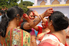 Religious Play With Vermilion. Beautiful Hindu women smear and play with vermilion during Sindur Khela traditional ceremony on the final day of Durga Puja Stock Photo