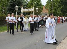 Religious procession at Corpus Christi Day. Galgaheviz, Hungary, Europe - June 26. Priest and assistants carrying the monstrance in the procession of Corpus Royalty Free Stock Image