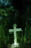 Religious reflection. A cross is reflected onto a pond by a cemetery Royalty Free Stock Photos