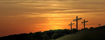 Religious representation with three crosses and nature landscape. Religious illustration with three backlit crosses with golden glitter and bokeh and nature royalty free stock images