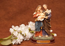 A Religious Scuplture With White Flowers Stock Image
