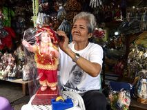 A religious shop owner fixes up a Child Jesus figurine Stock Image