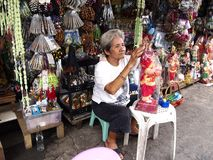 A religious shop owner fixes up a Child Jesus figurine Royalty Free Stock Image