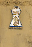 Religious symbols in Jodhpur, India. Official symbol of Jainism, known as the Jain Prateek Chihna, displayed on the yellow painted outdoor wall Royalty Free Stock Photos