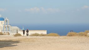 Religious tourists admiring view of church of panagia in Oia, Greece landmark. Stock footage stock video footage