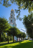 Religious tower with golden cupola under blue sky with tree alley in summer day Stock Photos