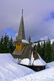 Religious winter. Small church in mountains, with fir forest and cludy sky in background Stock Images