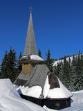 Religious winter. Small church in mountains, with fir forest and blue sky in background Stock Photo