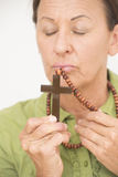 Religious woman kissing christian crucifix Royalty Free Stock Photo