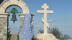 Religious woman looking at stone cross with hope. Symbol of church, religion. Stock footage stock video footage
