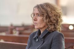 Religious woman sitting alone in a church pew royalty free stock photos