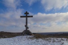 Religious wooden cross on a snowy hill. Against the blue sky. winter in the countryside Stock Photography