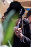 Religious young Jew in a black hat. JERUSALEM, ISRAEL - OKTOBER 16, 2016: Traditional market before the holiday of Sukkot. Religious young Jew in a black hat and Stock Photography