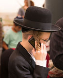 Religious young Jew talking on his mobile phone. JERUSALEM, ISRAEL - OKTOBER 16, 2016: Religious young Jew in a black hat and with side curls talking on his Royalty Free Stock Image