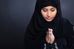 Muslim woman praying. Religious young Muslim woman praying over black background Stock Images