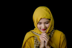 Religious young Muslim woman praying. Religious young Muslim woman praying over black background Royalty Free Stock Images
