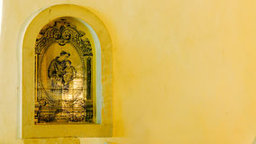Religous artwork on a wall. Religious artwork on the yellow wall of a building in Portugal Stock Photography