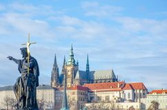 Religous statue on Charles Bridge with St Vitus Cathedral. In background Royalty Free Stock Images