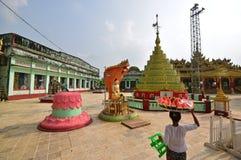 Relikskrin på den Shwemawdaw pagoden med en försäljare som bär den klippta vattenmelon på huvudet Royaltyfria Bilder