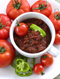 Relish tomato. Relish tomatoes with peppers onions and spices in a bowl on a tray Royalty Free Stock Image