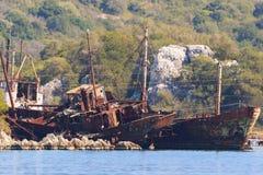 Relitti arrugginiti delle navi in acqua sulla riva Fotografia Stock