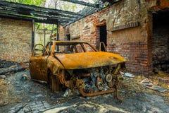 Relitto arrugginito e bruciato dell'automobile Immagini Stock
