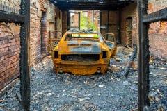 Relitto arrugginito e bruciato dell'automobile Immagine Stock