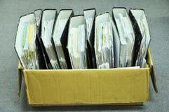 Reliure de dossiers dans une boîte sur le plancher de bureau Photographie stock libre de droits