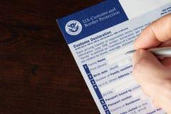 Rellenando encima de nosotros el impreso de la declaración de aduanas Imágenes de archivo libres de regalías