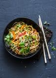 Rellene los tallarines vegetarianos tailandeses del udon de las verduras en un fondo oscuro, visión superior Comida vegetariana e Foto de archivo