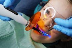 Relleno de los dientes de leche Clínica dental foto de archivo