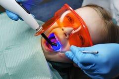 Relleno de los dientes de leche Clínica dental fotos de archivo
