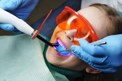 Relleno de los dientes de leche Clínica dental imagenes de archivo