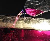 Relleno de un acuario de agua rosada usando una botella plástica en un relámpago oscuro imágenes de archivo libres de regalías